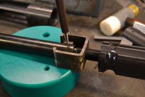 Using a pin punch and bench block, we remove the ejector pin. We remove the tool and slide the ejector and ejector spring out of the bolt.