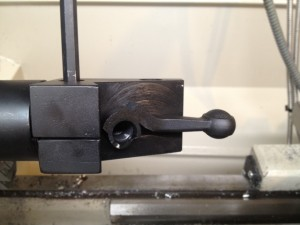 We mount the PTG jig into our three jaw chuck and secure the bolt handle in the fixture with a piece of brass shim stock.  At this point, we can still adjust the positioning of the bolt handle.