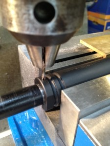 The muzzle brake is secured and stopped hole is drilled through the brake into the barrel.
