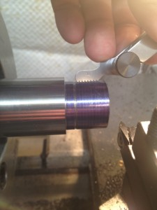 After a light pass is made with the threading tool, a thread gauge is used to ensure the threads are cut at the right pitch.