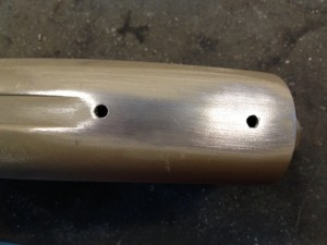 These are the two holes we need to fill.  The gun had previously been coated in Cerakote FDE.  Using a piece of 120 grit abrasive cloth. the finish is removed from the work area.