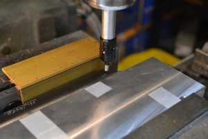 The action is attached to a Holland sine bar and secured in the milling machines vise.  The centerline of the receiver is determined and the location of the bolt release mortise determined.