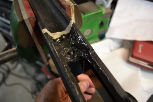 The front action screw is inserted through the bottom metal into the front pillar.  The stock is then gently lowered into the stock and the screws (front and rear) are slowly tightened.
