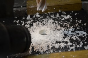We use a vacuum to remove the epoxy and fiberglass shavings from the stock.