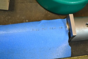 Painters tape is used to align the stamps so appropriate chamber markings can be made on the barrel.