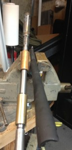 Here is a view of the setup used to remove the choke.  The two bushings are secured in place using e-clips supplied with the reamer.  The barrel is secured in a vice with bronze jaws.  The reamer, coated with Do-Drill oil is slowly turned to remove the fixed choke.