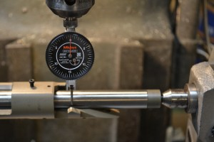 The front of the receiver ring is held in a 3-jaw vise on a rotary table.  The tailstock is used to secure the action mandrel.  A dial indicator is used to square the action on the milling machine.