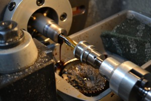 I cut the chamber with a SAMMI spec reamer secured in a floating reamer holder.  A pressurized coolant system pushes Do-Drill cutting oil through the barrel clearing the chips from the reamer.