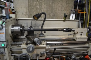 There are a few different ways to set up the choke reaming operation in the lathe. The vent rib does complicate the situation since you cannot use a steady rest.  I originally planned on machining a aluminum disk with a broach cut for the rib.  The disk would be forced over the barrel and allow the steady rest to support it.  Unfortunately, my steady rest didn't have a large enough capacity to support it.  The barrel is held in a three-jaw chuck and the reamer is held in the tailstock.