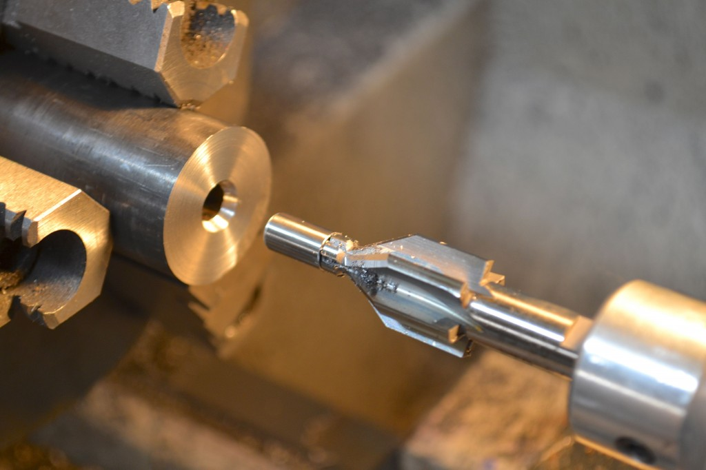 A 60-degree center drill is held in a floating reamer holder.  The live pilot is sized to the bore diameter.  The cut made by the center drill will receive the live center.