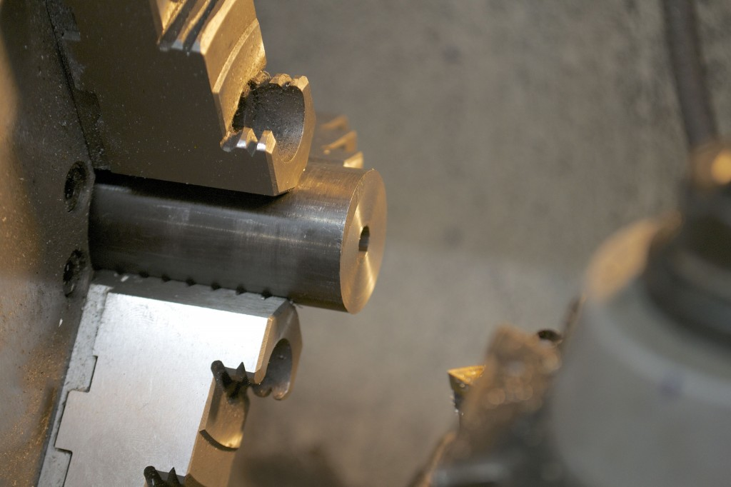 The blank is mounted in the lathe and the saw cut muzzle end is squared.