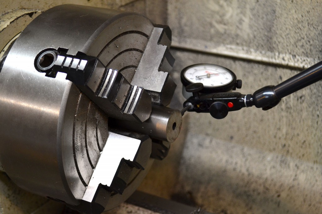 The barrel is secured in a four-jaw chuck and a dial indicator is used to dial it in.