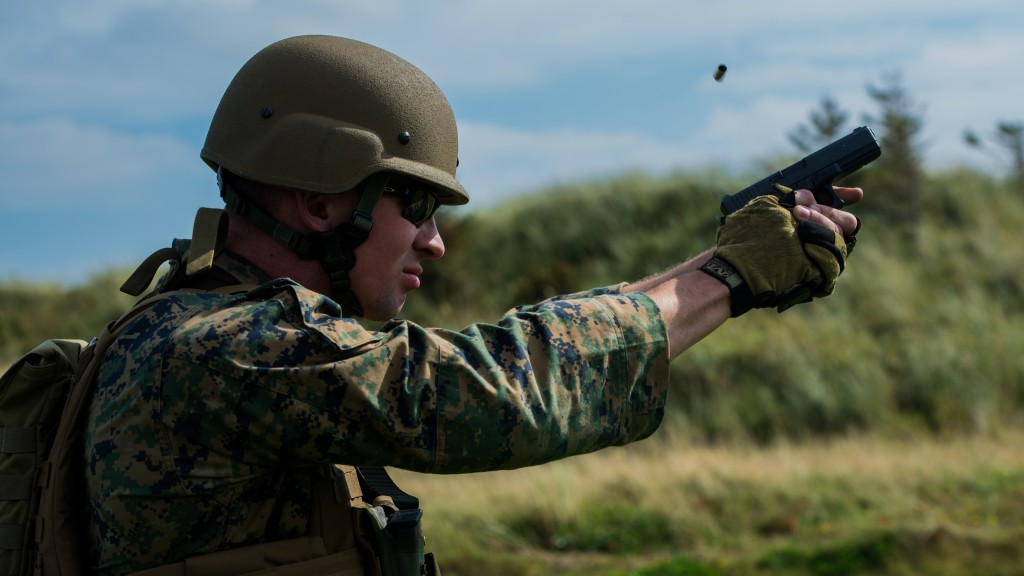 Sgt. Devin Hughes, a member of the Marine Corps Shooting Team, fires a round at a target during the Royal Marines Operational Shooting Competition at Altcar Range near Hightown, England, Sept. 8, 2014. The U.S. Marine Corps team dominated the pistol competitions, taking first place by more than 1,000 points. (U.S. Marine Corps photo by Cpl. Cameron Storm/Released)
