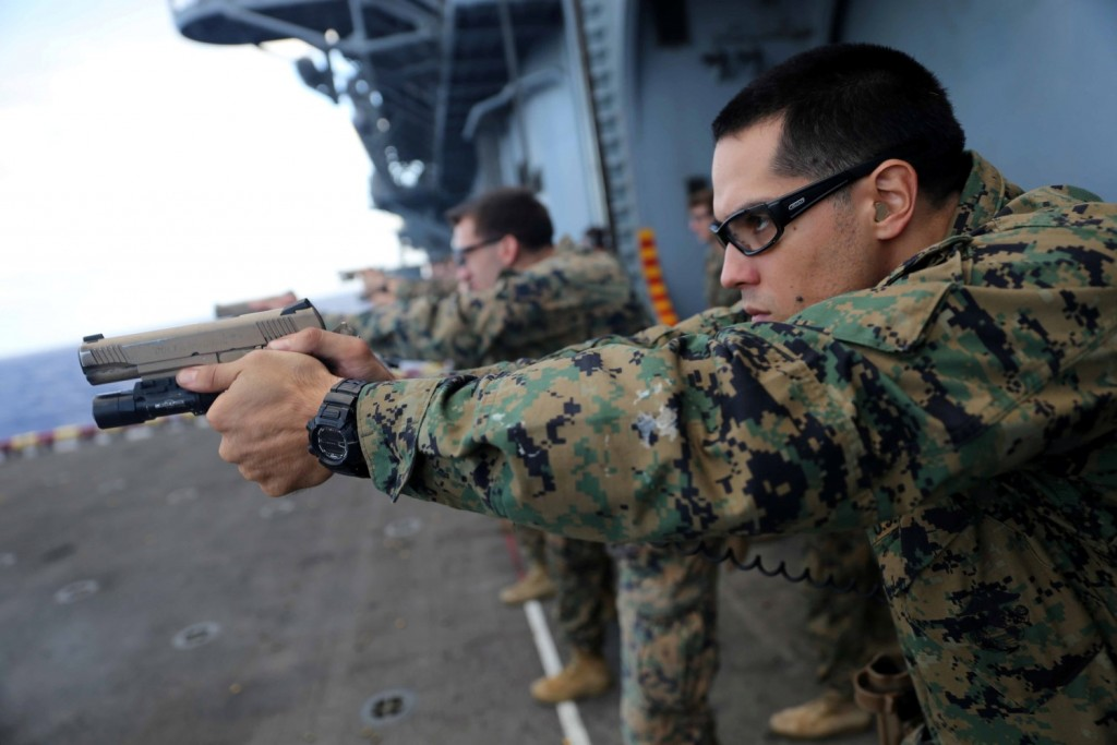 Sgt. Raymond Figueroa, a reconnaissance Marine with the Force Reconnaissance Detachment, 11th Marine Expeditionary Unit, sights in on his target during a pistol qualification aboard the amphibious assault ship USS Makin Island (LHD 8), Feb. 10. Embarked aboard the three ships of the Makin Island Amphibious Ready Group, the 11th MEU has provided a flexible, sea-based, crisis response force to regional commanders throughout its seven-month Western Pacific deployment. (U.S. Marine Corps photos by Cpl. Demetrius Morgan/Released)