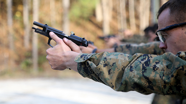 Marines paticipating in the EOTG Urban Sniper Course fire at designated targets as the students fire at targets aboard Marine Corps Base Camp Lejeune, N.C., December 4, 2014. Pistol qualifications are essential for room clearing and close-quarter shooting. After students fire the pistol they search and assess the area making sure the perimeter is safe. (U.S. Marine Corps photo by Pfc. Immanuel M. Johnson)